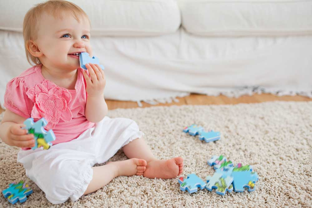 Infant playing on carpet